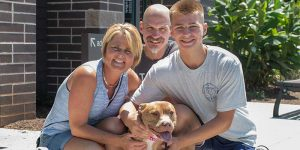 a family of three smiling outside the shelter with their newly adopted dog