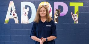 REbecca Guinn standing in front of the word Adopt at the LifeLIne Community Animal Center