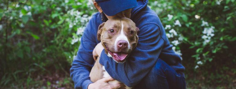 LifeLine volunteer hugging a shelter dog.