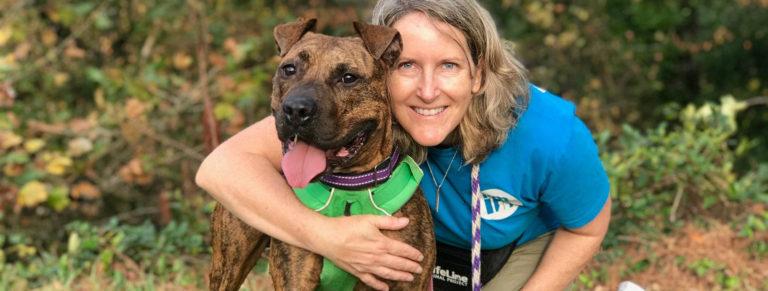 LifeLine volunteer hugging an adoptable shelter dog.