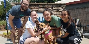 group of 4 people outdoors smiling with a dog.