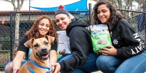 three women adopting a dog