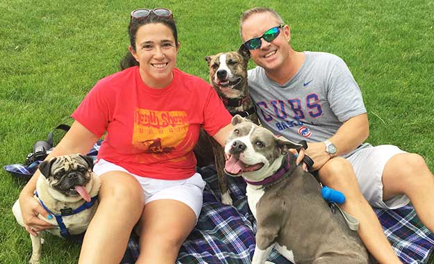 two volunteers with 3 smiling dogs