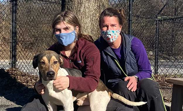 two volunteers with a dog