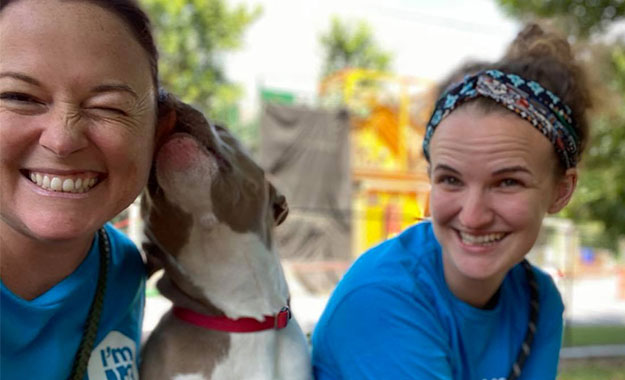 two volunteers smiling while a dog kisses their face