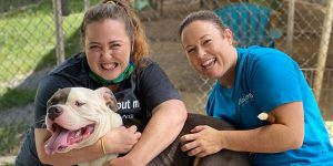 volunteers jamie and jessica smiling with a shelter dog